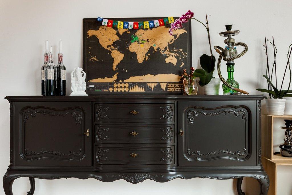 Une commode ancienne. Au-dessus une carte du monde avec les destinations de voyages personnelles
