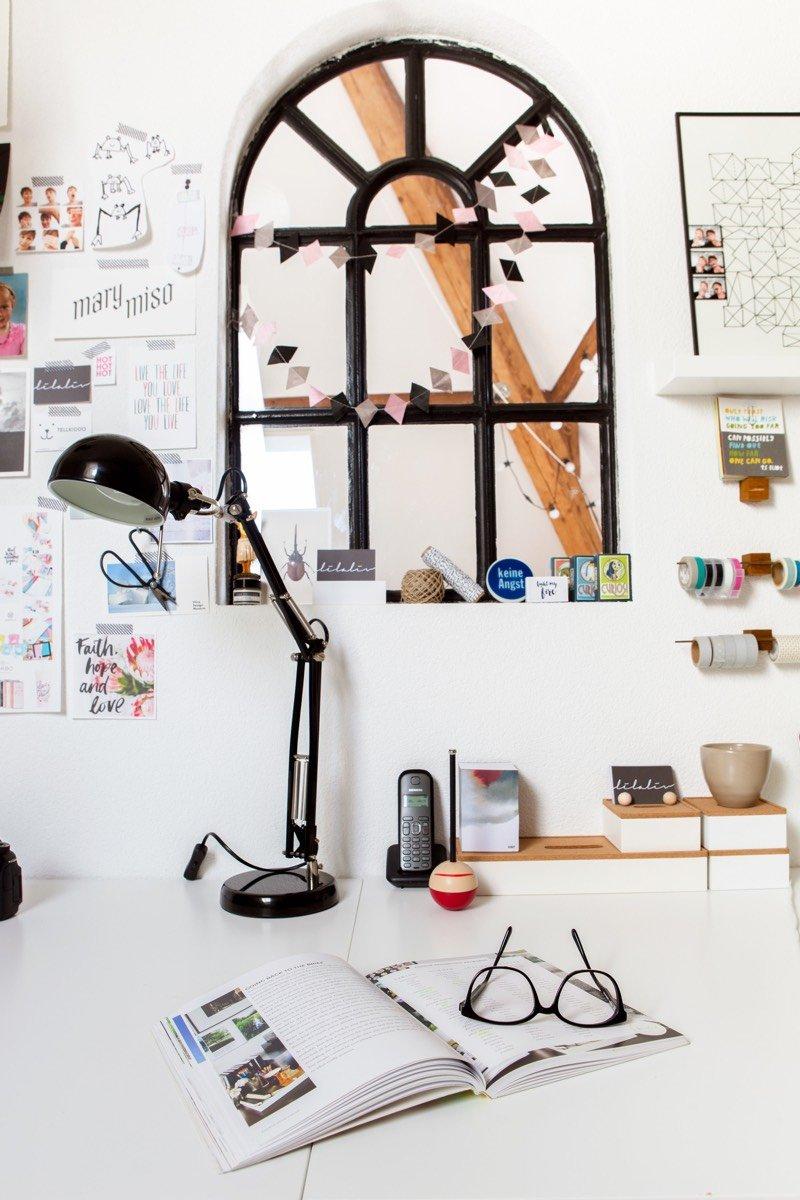 Un magazine ouvert est posé sur le bureau de Patrizia avec regard donnant dans la chambre de Liz.