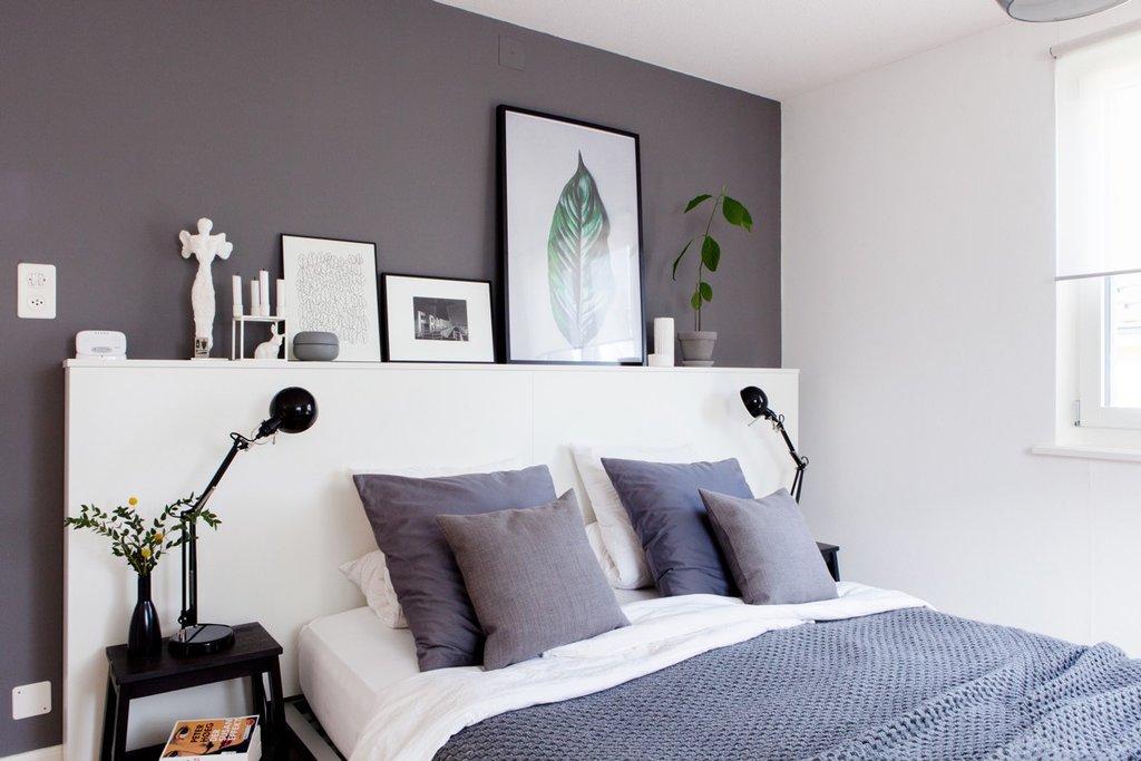 Lit avec coussins bleus et couverture devant un mur gris foncé.