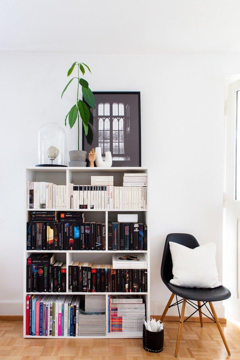 Auf einem weissen Bücherregal steht unter anderem eine Avocadopflanze im grau angestrichenen INGEFÄRA Blumentopf.