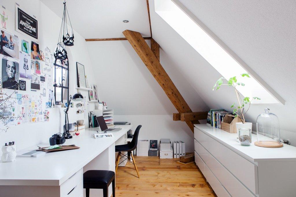 Weiss-schwarz eingerichteter Büroraum mit Dachschräge mit inspirierenden Bildern an der Wand.