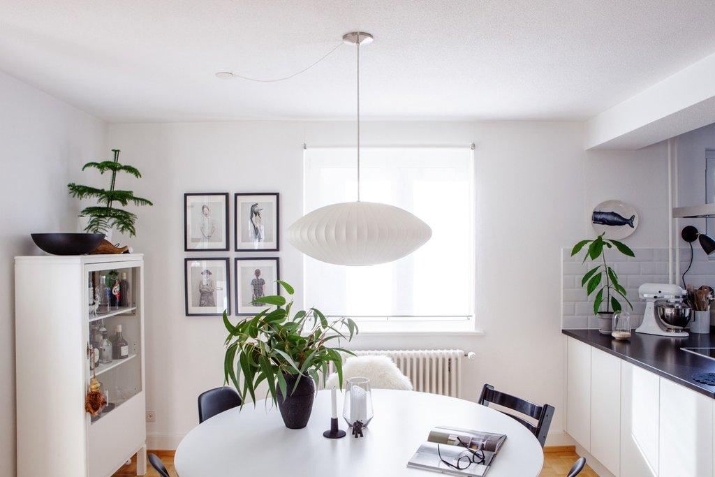 Einrichtung in Weiss, Schwarz und Grün: Über dem weissen Esstisch hängt eine George Nelson Lampe.
