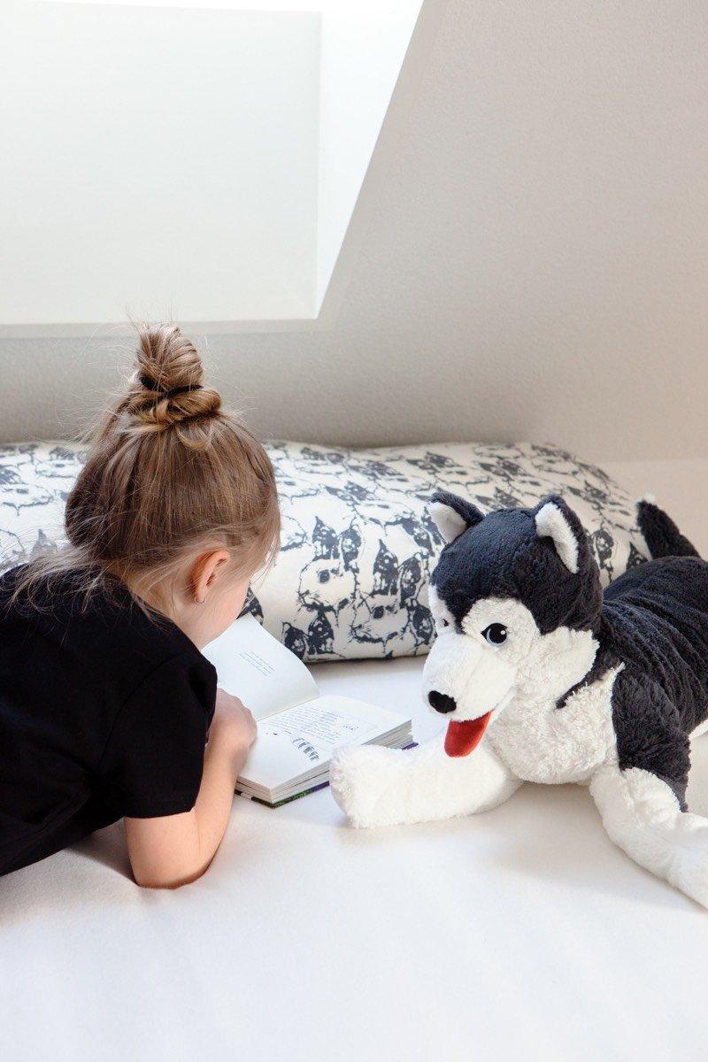Liv liest auf ihrem Bett mit dem LIVLIG Stofftier.