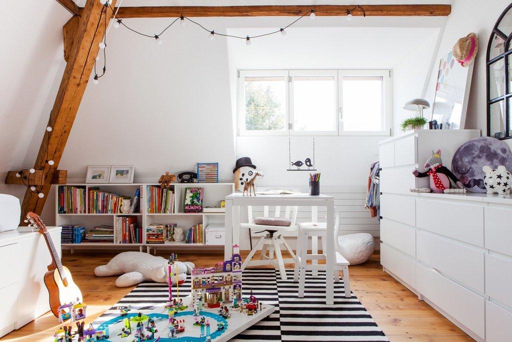 In Livs Kinderzimmer mit vielen weissen Möbeln sind Legos auf einer rollbaren Holzplatte.
