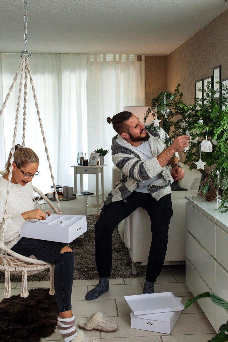 Marleen und Stefan schmücken im Wohnzimmer einen Tannenzweig mit Weihnachtsdeko