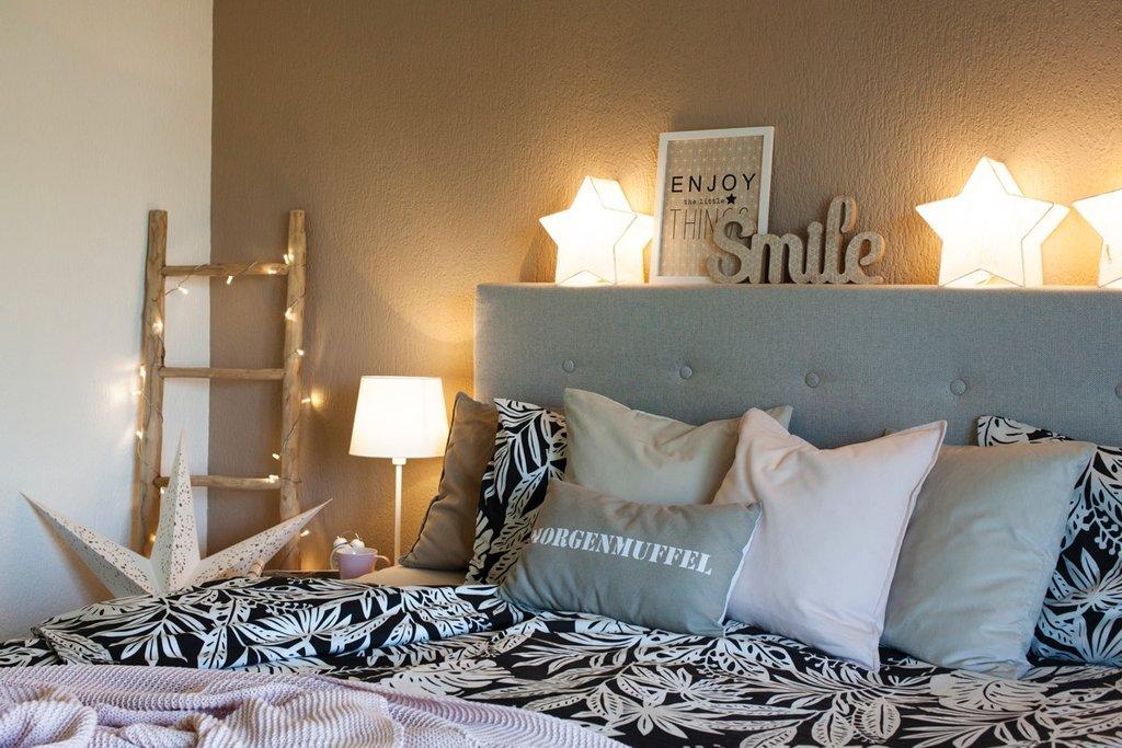 Das Doppelbett ist mit zahlreichen Kissen geschmückt und von Lämpchen beleuchtet
